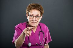 Portrait of senior lady doctor gesturing watching you. On black background Royalty Free Stock Images