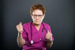 Portrait of senior lady doctor holding both fists. Looking mad on black background royalty free stock image