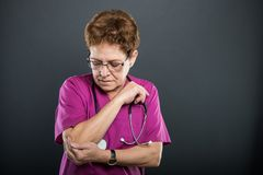 Portrait of senior lady doctor holding elbow like hurting. On black background with copyspace advertising area Stock Images