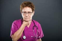 Portrait of senior lady doctor holding neck like hurting. On black background with copyspace advertising area Stock Images