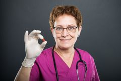 Portrait of senior lady doctor holding one pill. And smiling on black background Stock Image