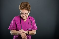 Portrait of senior lady doctor holding wrist like hurting. On black background with copyspace advertising area Stock Photography