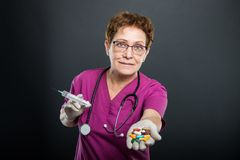 Portrait of senior lady doctor offering bunch of pills Stock Images