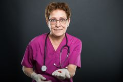Portrait of senior lady doctor offering one pill. And smiling on black background with copyspace advertising area Royalty Free Stock Photo