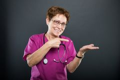Portrait of senior lady doctor pointing copyspace area. And smiling on black background Stock Image