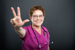 Portrait of senior lady doctor showing number three. And smiling on black background with copyspace advertising area Stock Photo