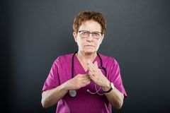 Portrait of senior lady doctor showing time out gesture. On black background Royalty Free Stock Photo