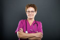 Portrait of senior lady doctor standing with arms crossed stock photo