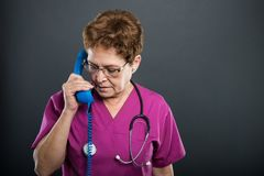 Portrait of senior lady doctor talking at telephone receiver. Portrait of senior lady doctor talking at big blue telephone receiver on black background with Stock Images