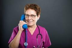 Portrait of senior lady doctor talking at telephone receiver. Portrait of senior lady doctor talking at big blue telephone receiver and smiling on black Stock Photos