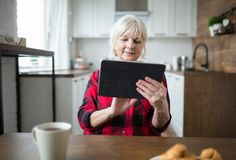 Senior lady using tablet at kitchen table. Portrait of senior lady using tablet at kitchen table Royalty Free Stock Image