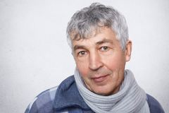 Portrait of senior male model with grey hair and wrinkled skin wears warm scarf on neck, looks confidently into camera, isolated o. Ver white background. People Royalty Free Stock Images
