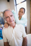 Portrait of senior male patient receiving neck massage from female therapist. At hospital ward Royalty Free Stock Photography