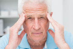 Portrait of senior male patient suffering from headache. In clinic Royalty Free Stock Images