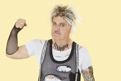 Portrait of senior male punk showing clenched fist over yellow background Royalty Free Stock Photos