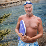 Composite image of portrait of senior male swimmer with swimming float. Portrait of senior male swimmer with swimming float against flowing river in forest Royalty Free Stock Image