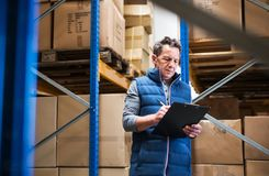 Portrait of a senior male warehouse worker or a supervisor. Portrait of a senior male warehouse worker or a supervisor with clipboard, making notes Stock Image