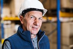 Portrait of a senior male warehouse worker or a supervisor. Close up. Portrait of a senior male warehouse worker or a supervisor with white hardhat. Close up Royalty Free Stock Images