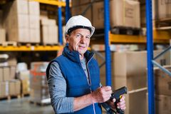 Portrait of a senior male warehouse worker or a supervisor. Portrait of a senior male warehouse worker or a supervisor with handheld barcode scanner Stock Image