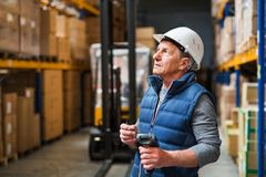 Portrait of a senior male warehouse worker or a supervisor. Portrait of a senior male warehouse worker or a supervisor with handheld barcode scanner Royalty Free Stock Image