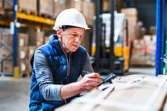Portrait of a senior male warehouse worker or a supervisor. Portrait of a senior male warehouse worker or a supervisor with handheld barcode scanner Stock Photography
