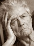 Unhappy Senior Man. Sepia portrait of senior man leaning head on hand Royalty Free Stock Images