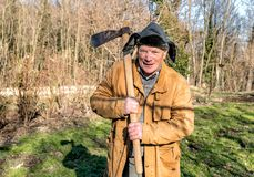 Senior man with ax over his shoulder in the autumn garden. Portrait of Senior man with ax over his shoulder in the autumn garden Stock Image