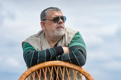 Portrait of senior man in black sunglasses leant on a wicker chair back and looking Royalty Free Stock Image