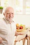 Portrait of senior man at breakfast. Portrait of happy senior man sitting at breakfast table, holding newspaper, smiling at camera Stock Images