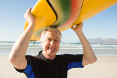 Portrait of senior man carrying surfboard at beach Stock Image