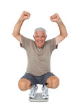 Portrait of a senior man cheering on weight scale Royalty Free Stock Images