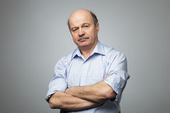Portrait of senior man with crossed hands. Royalty Free Stock Photo