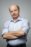 Portrait of senior man with crossed hands. Stock Photo