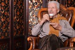 Portrait of senior man drinking at home stock photo
