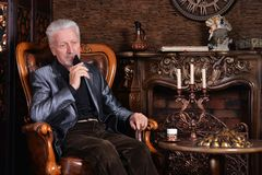 Portrait of senior man drinking at home stock photography