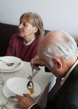 Portrait of a senior man eating a soup outdoor. Wife is on fundal Royalty Free Stock Image