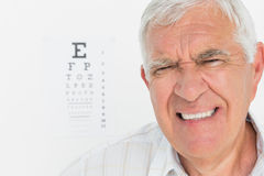 Portrait of a senior man with eye chart in background Royalty Free Stock Photo