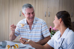 Portrait of senior man and female doctor having cake in living room Royalty Free Stock Images