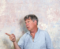 Portrait of senior man in front of grungy old wall Stock Image