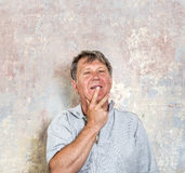 Portrait of senior man in front of grungy old wall Stock Images
