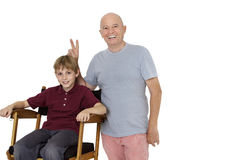 Portrait of senior man gesturing peace sign while pre-teen boy sitting on director's chair over white background Royalty Free Stock Images