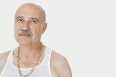Portrait of senior man with gold chain over gray background Royalty Free Stock Images
