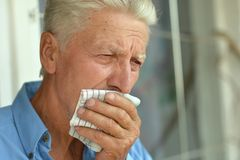 Senior man coughing. Portrait of a senior man with handkerchief coughing royalty free stock photography