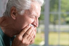 Portrait of senior man having a toothache, holding handkerchief royalty free stock images