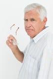 Portrait of a senior man holding glasses Stock Images