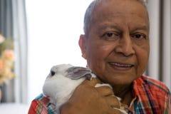 Portrait of senior man holding rabbit at nursing home. Close up portrait of senior man holding rabbit at nursing home Royalty Free Stock Images