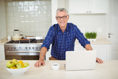 Portrait of senior man with laptop in kitchen Royalty Free Stock Images