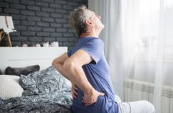 Senior man with lower back pain siting on bed. Portrait of senior man with lower back pain siting on bed royalty free stock images