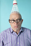 Portrait of senior man making face with shuttlecock on head Royalty Free Stock Images