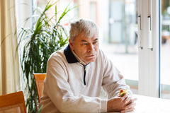 Portrait of senior man near window, indoor. Royalty Free Stock Photography